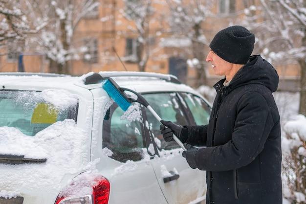 Maschio adulto pulire il parabrezza dell'auto dalla neve nella bufera di neve