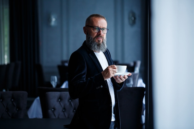 Un mentore maschio adulto, un regista, un uomo d'affari con gli occhiali e un vestito beve caffè e si riposa. concetto di giornata lavorativa