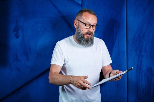 Mentore maschio adulto, regista, uomo d'affari con gli occhiali e un vestito che studia documenti mentre è seduto al tavolo. concetto di giornata lavorativa