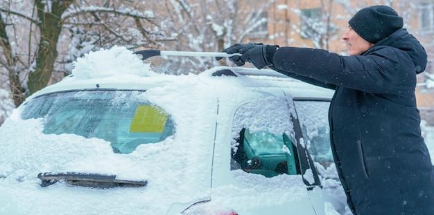 Maschio adulto che rimuove la neve dal tetto dell'auto con una spazzola nella stagione invernale