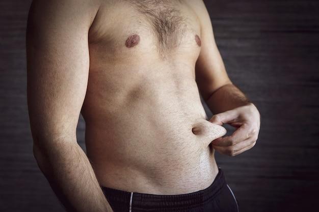 Un maschio adulto si schiaccia una piega di grasso sullo stomaco. un uomo con una bella figura si stringe la pelle sullo stomaco.