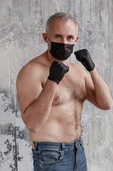 Un uomo adulto con una maschera medica nera e guanti neri