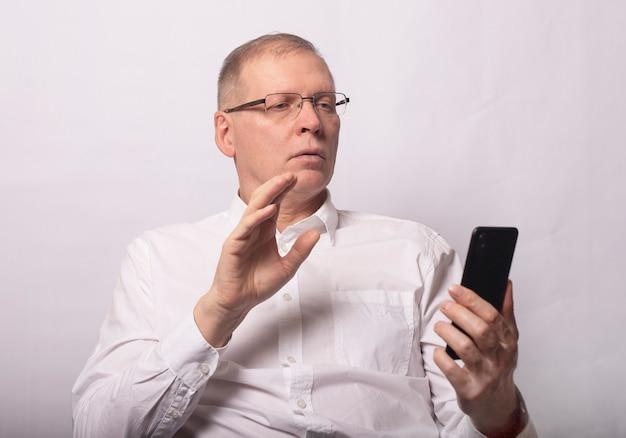 Uomo adulto in chat con il partner per telefono, teleconferenza, vista frontale. saluto dell'uomo d'affari agitando allo smartphone.