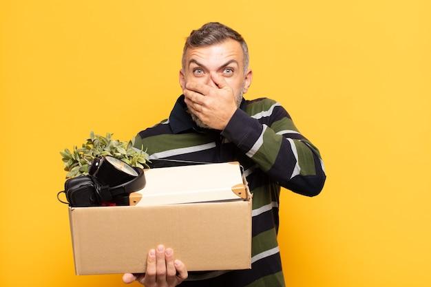 Uomo adulto che copre la bocca con le mani con un'espressione scioccata e sorpresa, mantenendo un segreto o dicendo oops