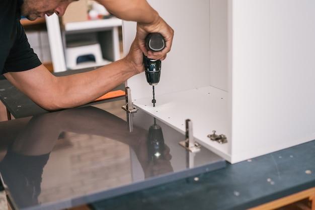 Uomo adulto che perfora una superficie di legno di un mobile per la cucina