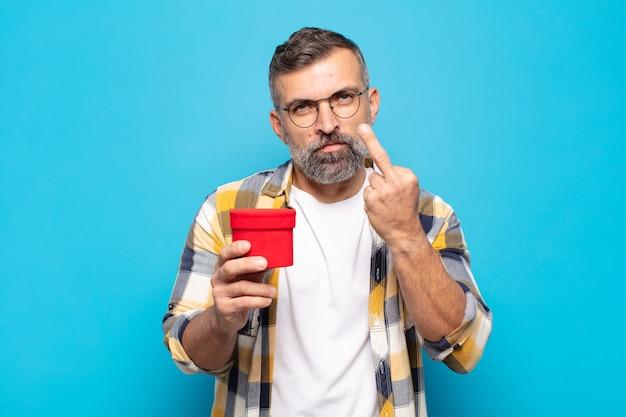Uomo adulto che si sente arrabbiato, infastidito, ribelle e aggressivo, lancia il dito medio, reagisce