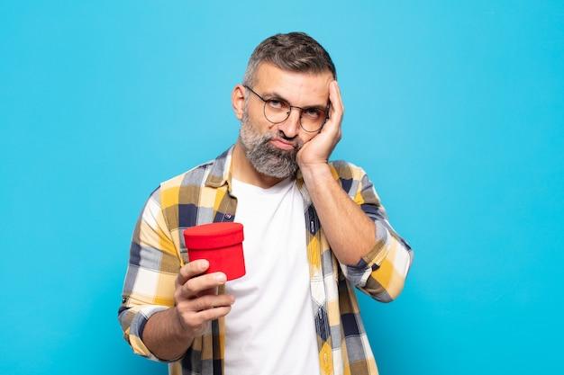 Uomo adulto che si sente annoiato, frustrato e assonnato dopo un compito noioso, noioso e noioso, tenendo la faccia con la mano