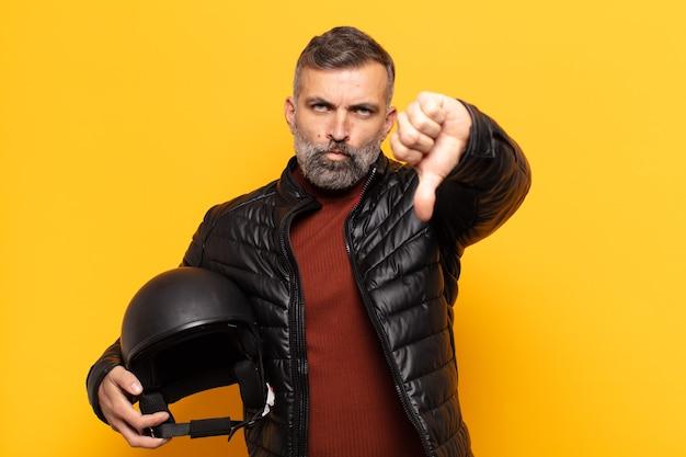 Uomo adulto che si sente arrabbiato, arrabbiato, infastidito, deluso o scontento, mostrando i pollici verso il basso con uno sguardo serio