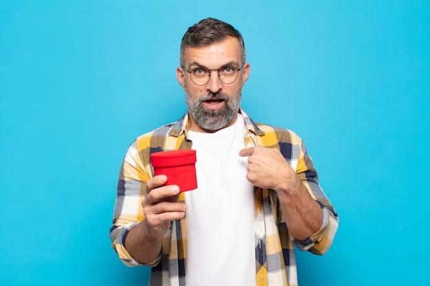 Uomo adulto che si sente felice, sorpreso e orgoglioso, indicando se stesso con uno sguardo eccitato e stupito