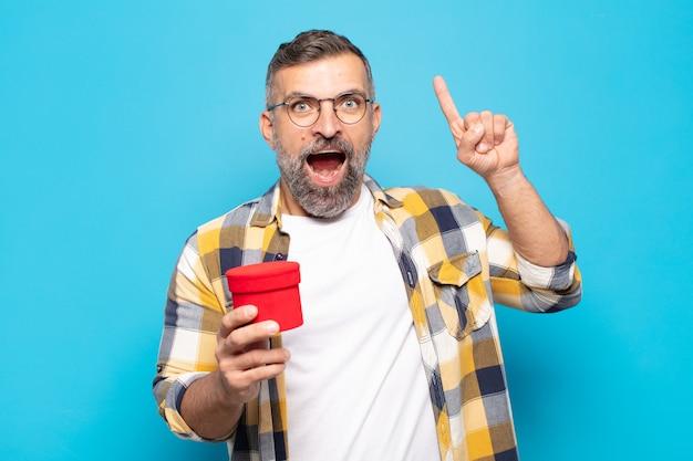 Uomo adulto che si sente un genio felice ed eccitato dopo aver realizzato un'idea, alzando allegramente il dito, eureka!
