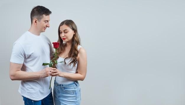 Un uomo adulto regala una rosa rossa a un'affascinante donna bionda con indosso una maglietta bianca