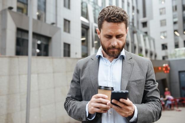 Uomo adulto in abito grigio guardando il cellulare in mano, mentre in piedi con il caffè da asporto davanti al moderno centro business