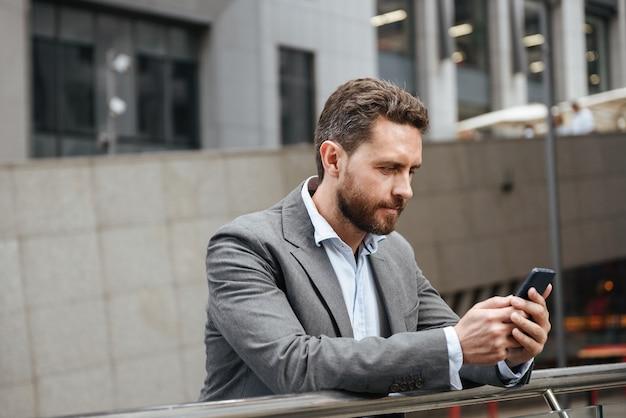 Uomo adulto in abito grigio che digita o legge un messaggio di testo nel telefono cellulare, mentre si trova di fronte al moderno edificio per uffici