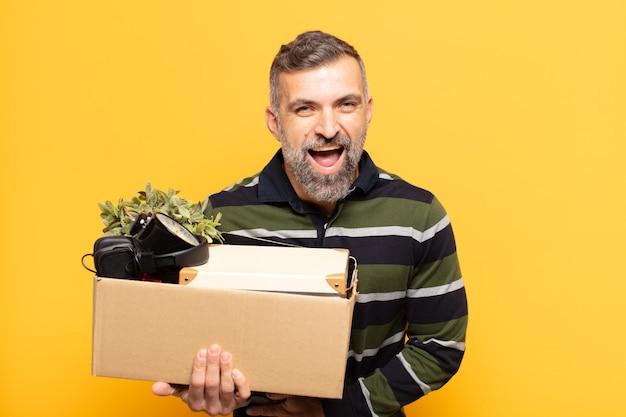Uomo adulto che ride ad alta voce per qualche scherzo esilarante, sentendosi felice e allegro, divertendosi