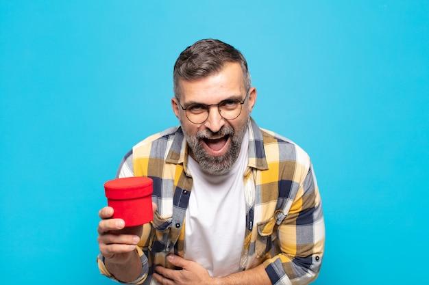 Uomo adulto che ride ad alta voce per uno scherzo esilarante, sentendosi felice e allegro, divertendosi
