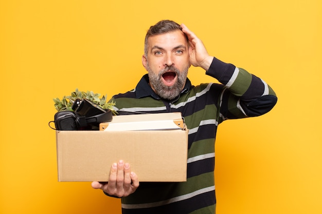 Uomo adulto che sembra felice, stupito e sorpreso, sorridente e realizzando incredibili e incredibili buone notizie
