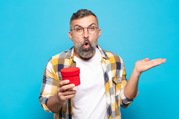Uomo adulto che sembra sorpreso e scioccato, con la mascella caduta tenendo un oggetto con una mano aperta sul lato