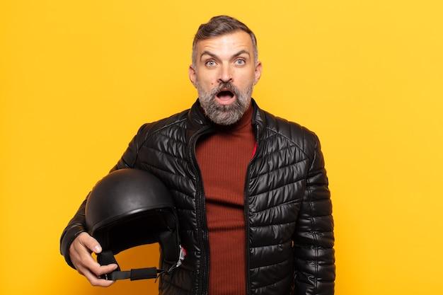 Uomo adulto che sembra molto scioccato o sorpreso, fissando con la bocca aperta dicendo wow