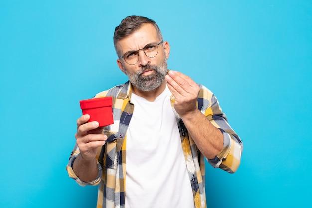 Uomo adulto che fa gesto di capice o denaro, dicendoti di pagare i tuoi debiti!