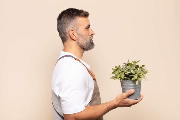 Uomo adulto sulla vista di profilo che cerca di copiare lo spazio davanti, pensare, immaginare o sognare ad occhi aperti