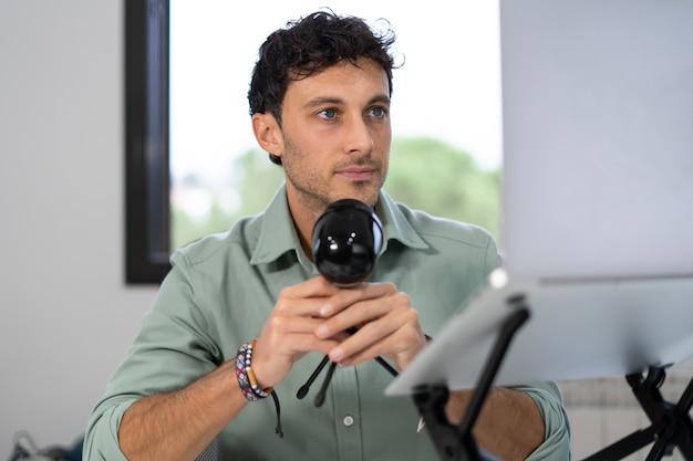 L'uomo adulto registra un podcast da casa, concetto di lavoro a domicilio digitale, giovane imprenditore