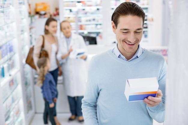Uomo adulto che compera in una farmacia
