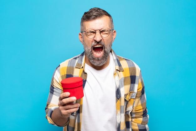 Uomo adulto che grida in modo aggressivo, sembra molto arrabbiato, frustrato, oltraggiato o infastidito, urlando no