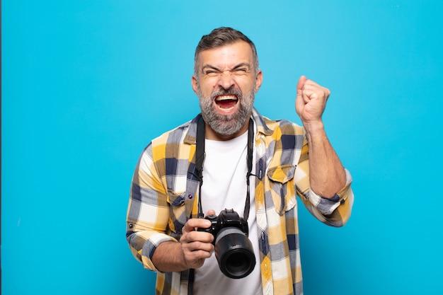 Uomo adulto che grida in modo aggressivo con un'espressione arrabbiata o con i pugni chiusi per celebrare il successo
