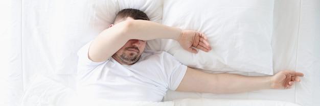 Un uomo adulto dorme in camera da letto su un letto grande concetto di uomo non iniziato