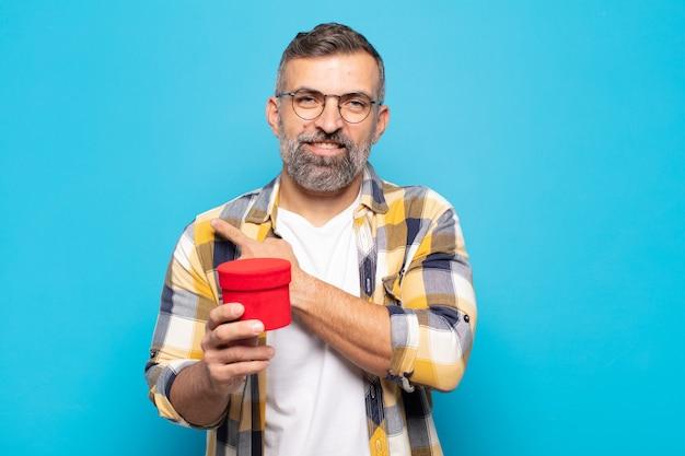 Uomo adulto che sorride allegramente, si sente felice e indica di lato e verso l'alto, mostrando l'oggetto nello spazio della copia