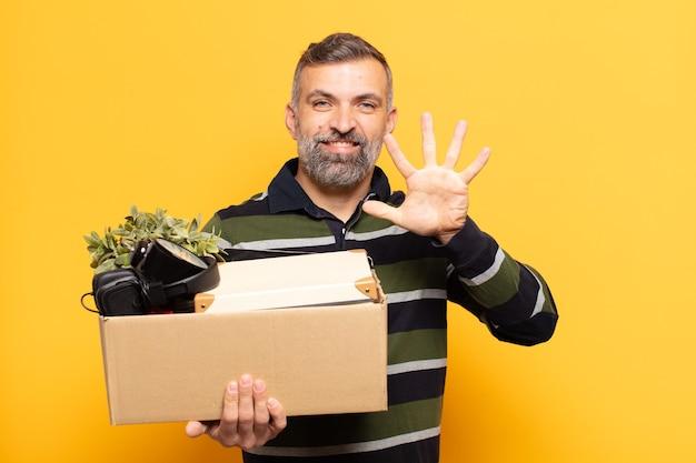 Uomo adulto che sorride e sembra amichevole, mostrando il numero cinque o quinto con la mano in avanti, conto alla rovescia