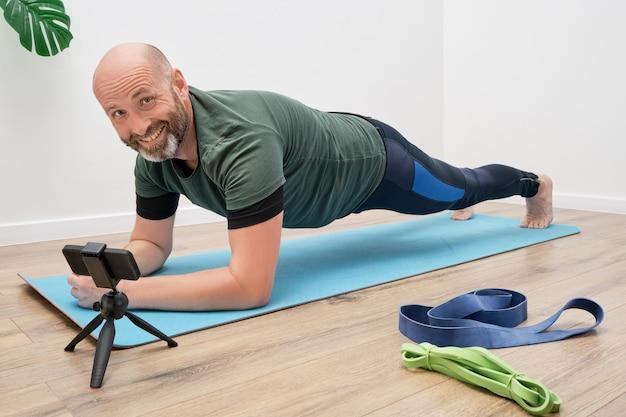 Uomo adulto in abbigliamento sportivo sta facendo esercizi sul tappetino davanti allo smartphone durante un allenamento online.