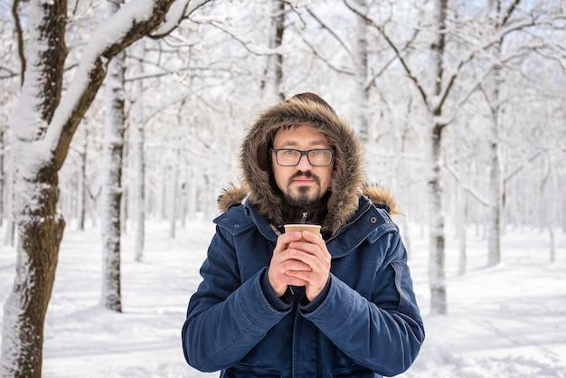 Un uomo adulto che indossa una giacca a vento con cappuccio e pelliccia in testa. tema invernale e gelo. caffè o tè in un bicchiere di carta nelle sue mani. ritratto dell'uomo bello caucasico nel giorno di congelamento.