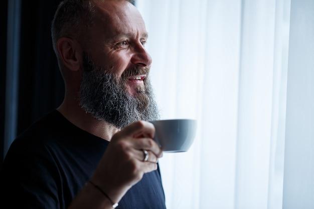 Un uomo adulto con la barba beve caffè e guarda fuori dalla finestra. concetto di ricreazione sul campo della giornata lavorativa working