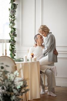 Uomo adulto e donna che si abbracciano seduti vicino a un tavolo festivo rotondo