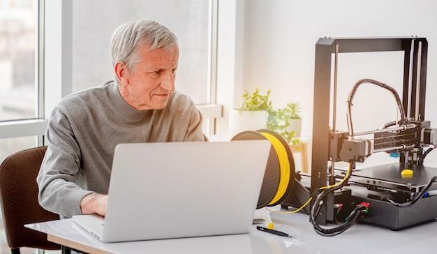 Uomo adulto che lavora a un progetto di design con stampante 3d e laptop