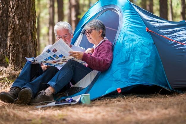 Coppia adulta matura in pensione che si gode il campeggio selvaggio all'aperto nella foresta guardando insieme una mappa cartacea per scegliere la prossima destinazione avventurosa da vedere e da vivere - concetto di turismo di viaggio