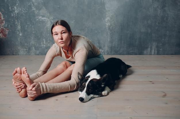 Donna matura adulta che fa yoga a casa in salotto con l'animale domestico del cane di corgi