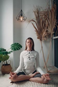 Donna matura adulta che fa yoga a casa soggiorno con tutorial online sul computer portatile