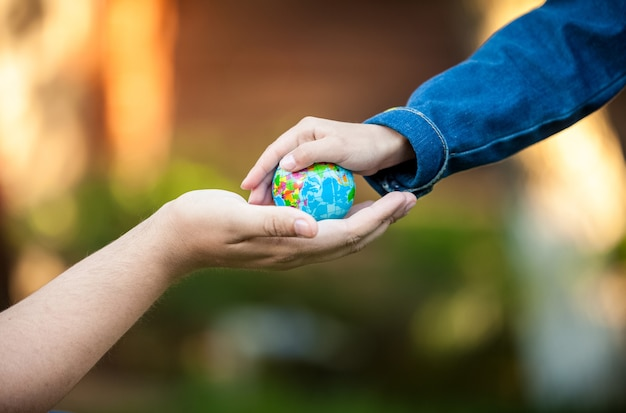 Mano di uomo adulto e mani di bambina che tengono il pianeta terra