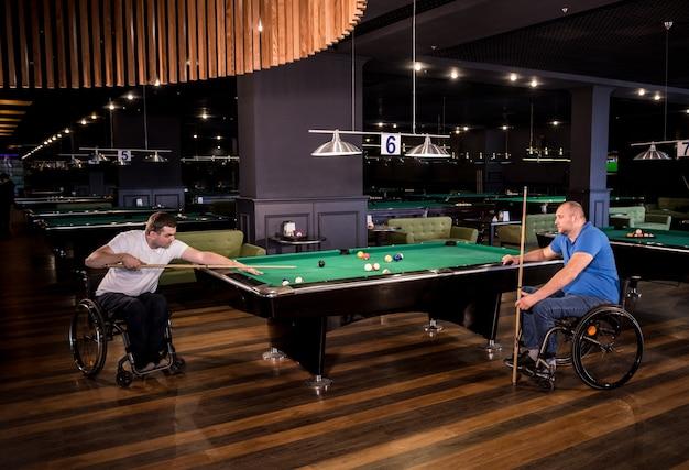 Uomini adulti con disabilità in sedia a rotelle giocano a biliardo nel club