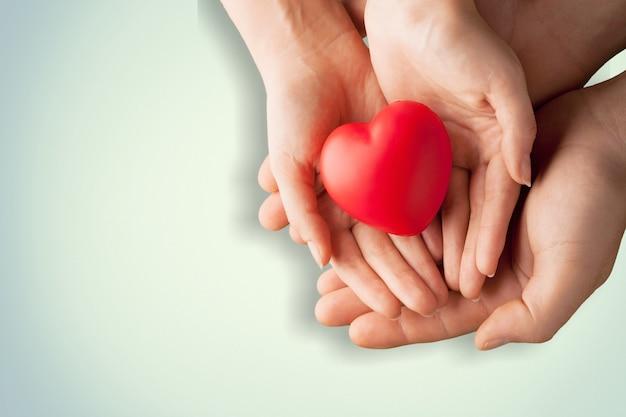 Un adulto, una madre e un bambino tengono in mano un cuore rosso. concetto di beneficenza, assicurazione sanitaria,