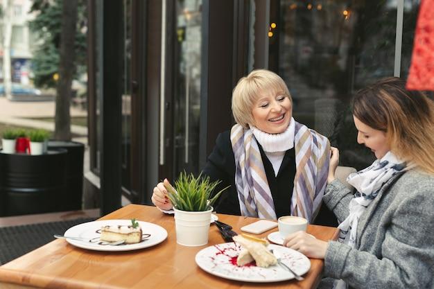 La madre e la figlia adulte si siedono a un tavolo di legno