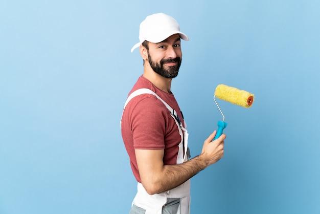 Uomo adulto del pittore sopra la parete blu isolata