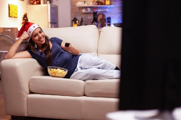Persona adulta che sorride mentre guarda un film di natale sdraiato sul divano