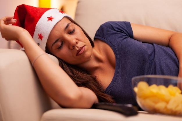 Persona adulta con cappello da babbo natale che dorme sul divano dopo aver visto un film di intrattenimento di dicembre