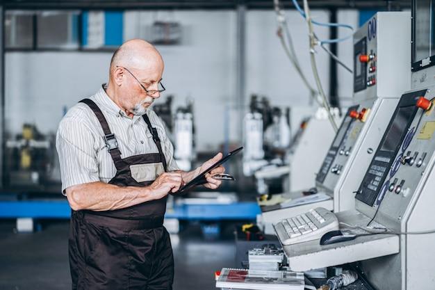 Lavoratore professionista adulto nella fabbrica che lavora con macchinari. un uomo sta in piedi con un tablet in mano, controllando la manutenzione delle macchine