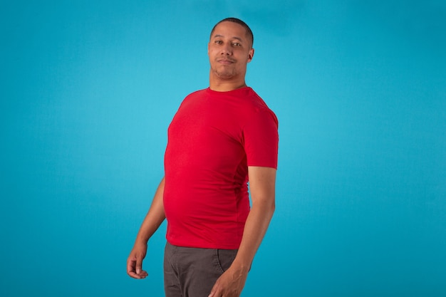Adulto in camicia rossa su sfondo blu, che fa varie espressioni facciali.