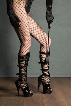 Giochi di sesso per adulti. le gambe della ragazza sexy in calze a rete e stivali fetish con i tacchi alti con la frusta si preparano per la punizione. - immagine