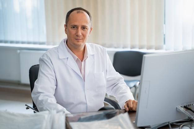 Il medico sorridente adulto sta sedendosi rilassato allo scrittorio in ufficio. il computer è davanti al dottore. scrub bianchi. avvicinamento.